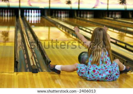 A young gal at the bowling alley - playing 'crazy bowl' - a game where you do a variety of different ways of rolling the ball down the alley - like with your feet etc. - stock photo