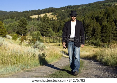 A young gangster in a fedora hat and black overcoat walks down a dirt road carrying a gun