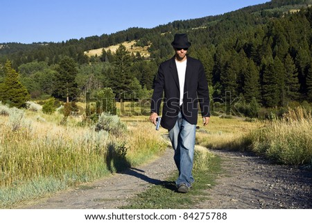 A young gangster in a fedora hat and black overcoat walks down a dirt road carrying a gun - stock photo