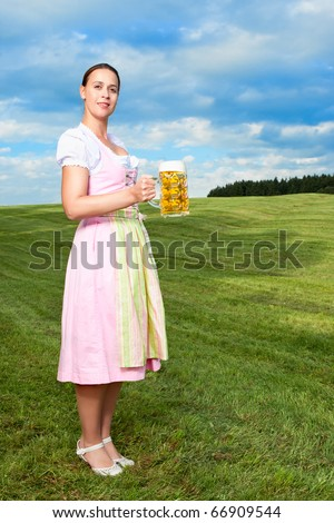 A young German girl in a Bavarian field with an Oktoberfest beer