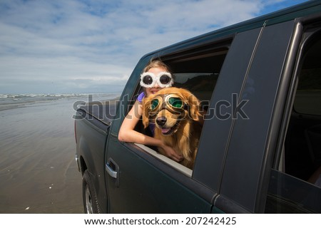 a young girl and a happy golden retriever dog wearing goggles with their heads out the window of a vehicle while driving on the beach - stock photo