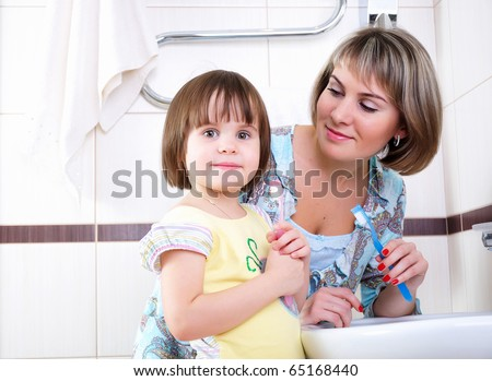 A young girl and her mother woke up early in the morning brushing his teeth in his bathroom - stock photo