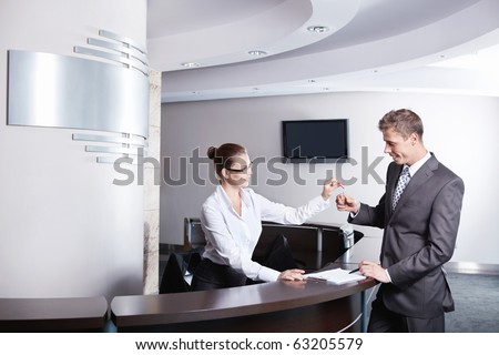 A young girl at the reception gave the keys to businessman - stock photo