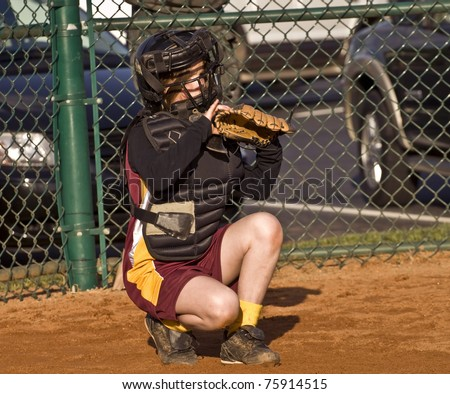 A young girl behind home plate watching intently ready to make a play. - stock photo