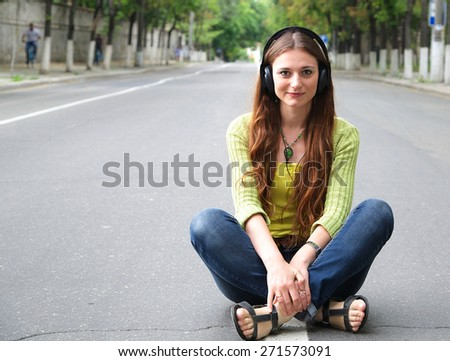 A young girl between 20 and 30 years old in headphones is sitting in the middle of the roadway. Free space for a text - stock photo