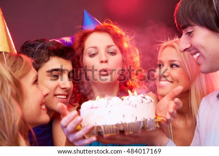 A young girl blowing out candles on her birthday cake among her four friends that are looking at her and the cake and smiling