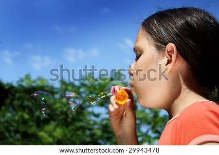 a young girl blows a bubble - stock photo