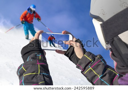 A young girl by mobile phone photographed of skiers - stock photo
