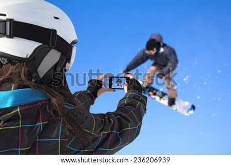 A young girl by mobile phone photographed of snowboarder jump