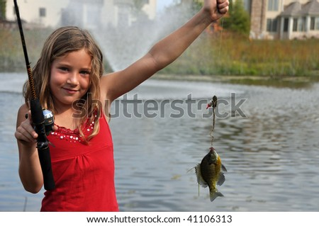 a young girl catches a fish - stock photo