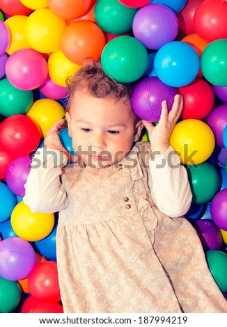 A young girl child having fun playing with colorful plastic balls