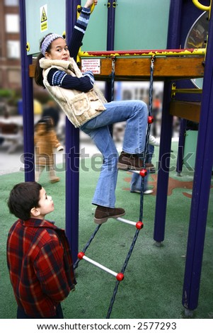 A young girl climbs on the ladder to a playground structure, watched by her younger brother - stock photo