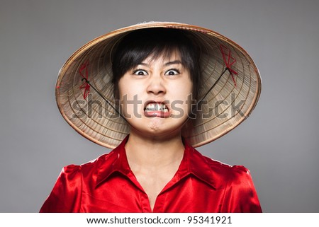 A young girl comically angry with traditional Asian hat - stock photo