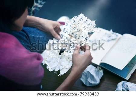 A young girl concentrating and staring at japanese characters written on a crumpled, burnt paper. - stock photo