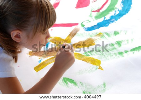 A young girl concentrating on a picture she is painting - stock photo