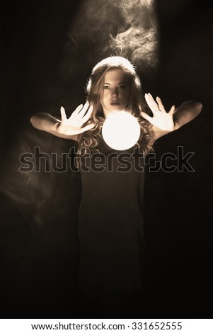 A young girl conjures using magic ball. Sepia.