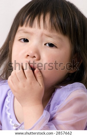 A young girl coughs and is not feeling well. - stock photo