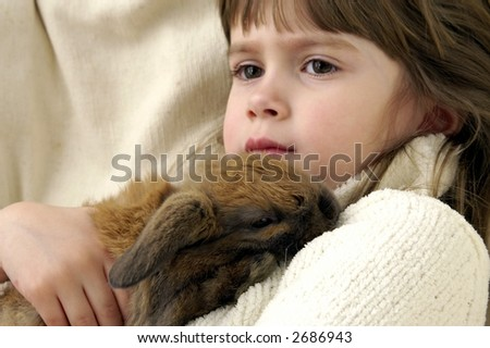 A young girl cuddles with her rabbit - stock photo