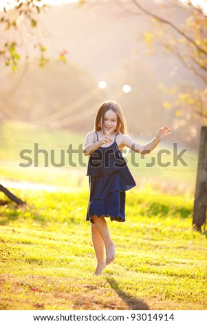 A young girl dancing in a field.  There is haze in the background. - stock photo