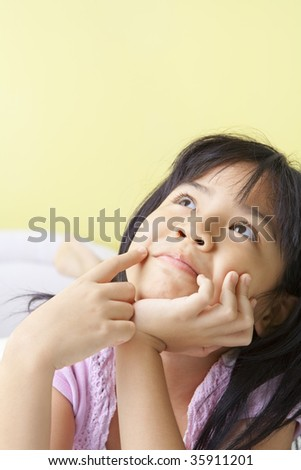 a young girl daydreaming in her bedroom - stock photo