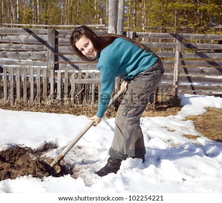 A young girl digs the garden in early spring. Russia. The extreme north.