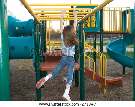 A young girl does the hanging walk along the monkey bars. - stock photo