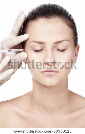A young girl doing a shot in the corner of his eye on a white background - stock photo