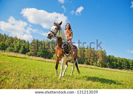 A young girl dressed as an Indian rides a paint horse - stock photo