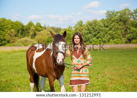 A young girl dressed as an Indian  with a paint horse