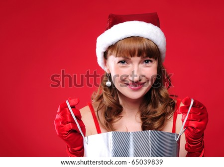 a young girl dressed as Santa Claus on a red background is engaged in shopping. A girl holding shopping bags. Happy New Year and Merry Christmas!