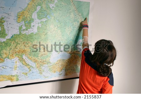 A young girl during a school test of geography, pointing with her hand over a europe map - stock photo
