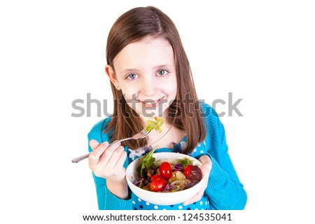 a young girl eating a healthy salad