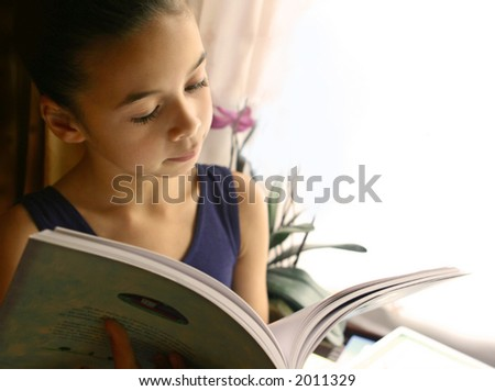 A young girl engross in her storybook, beautifully lit by the light from the window. - stock photo