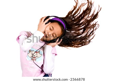 A young girl enjoying her music , hair in the air showing lots of movement. - stock photo