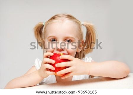 A young girl enjoys eating a apple. - stock photo