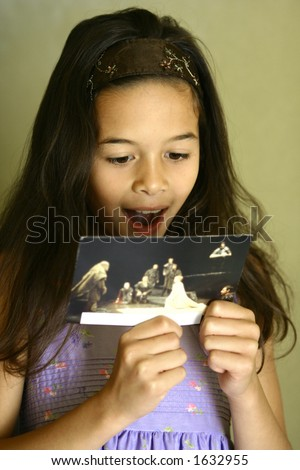 A young girl feeling very happy and glad after receiving a postcard from her friend