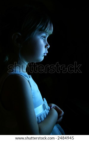 A young girl gazing out of a window - stock photo