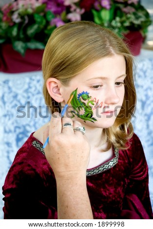 A young girl gets her face painted at a renaissance festival. - stock photo