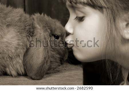 A young girl giving her bunny kisses - stock photo