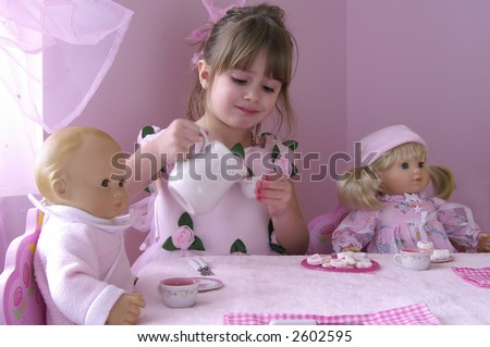 A young girl having a tea party with her baby dolls - stock photo