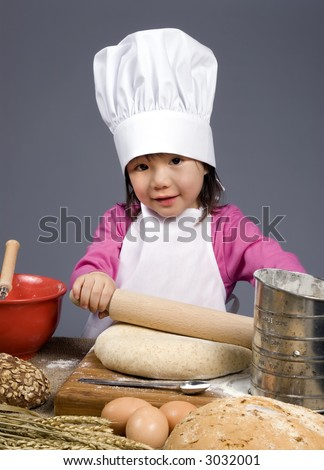 A young girl having fun in the kitchen making a mess....I mean making something special..... Education, learning, cooking, childhood - stock photo