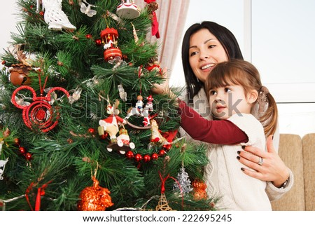 A young girl helps her mother to decorate the family Christmas tree