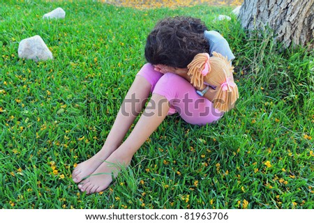 A young girl hides her face and cries under a tree on the grass while holding her stuffed toy doll. - stock photo