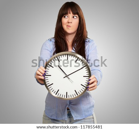 A Young Girl Holding A Clock And Making Face On Grey Background