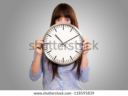 A Young Girl Holding A Clock On grey Background - stock photo