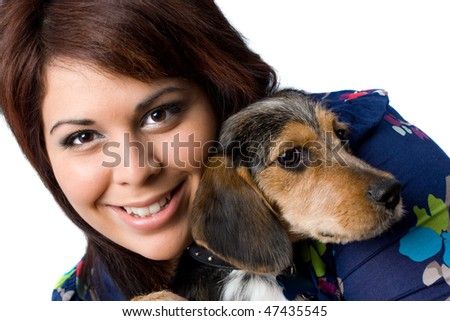 A young girl holding a cute mixed breed beagle yorkie dog isolated on a white background. - stock photo