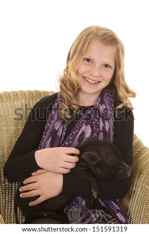 A young girl holding a little pig in her arms with a  smile on her lips. - stock photo