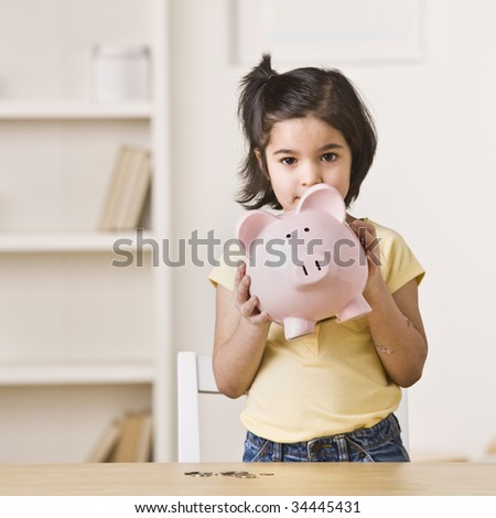 A young girl holding a pink piggy bank.  Square framed shot. - stock photo