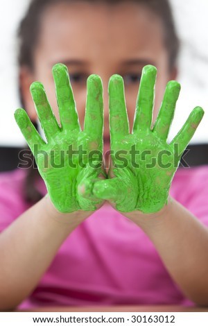 A young girl holding up her hands covered in green paint, the focus is on the hands in the foreground.