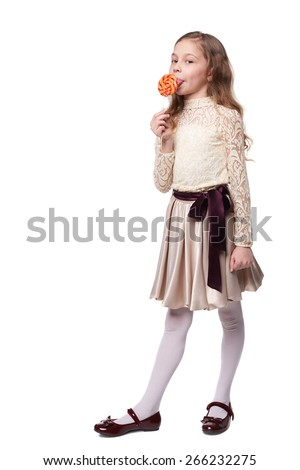 A young girl holds a large spiral lollypop isolated on white  - stock photo
